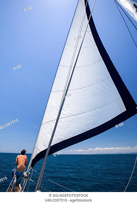 Man sitting on bow of sailboat, Belize