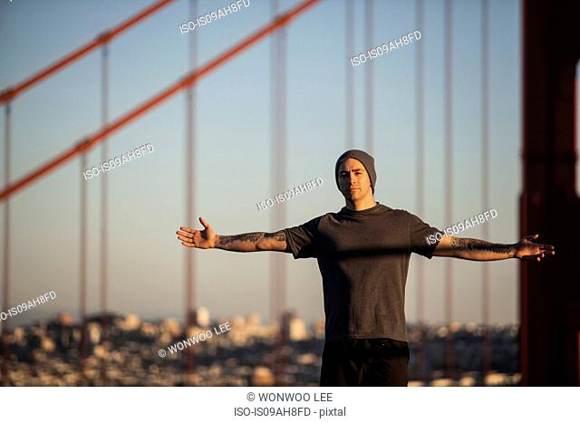 Young male runner with open arms in front of golden gate bridge