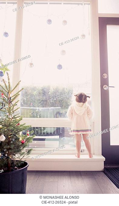 Curious girl on window ledge below Christmas ornaments