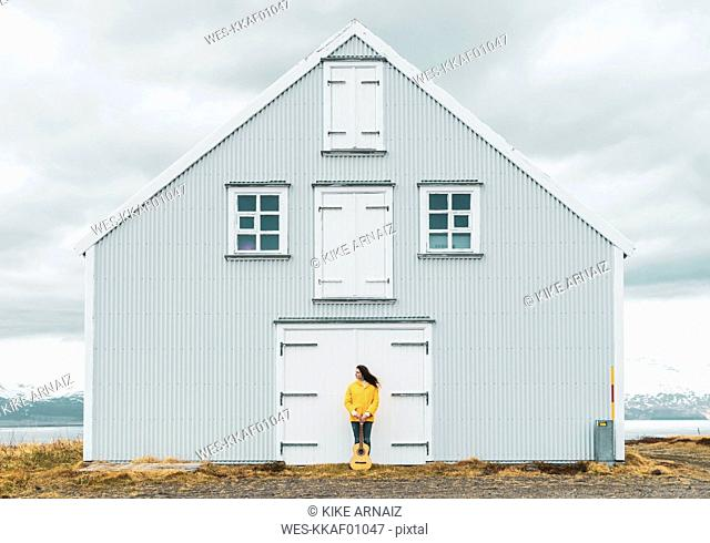 Iceland, woman with guitar standing at lonely house