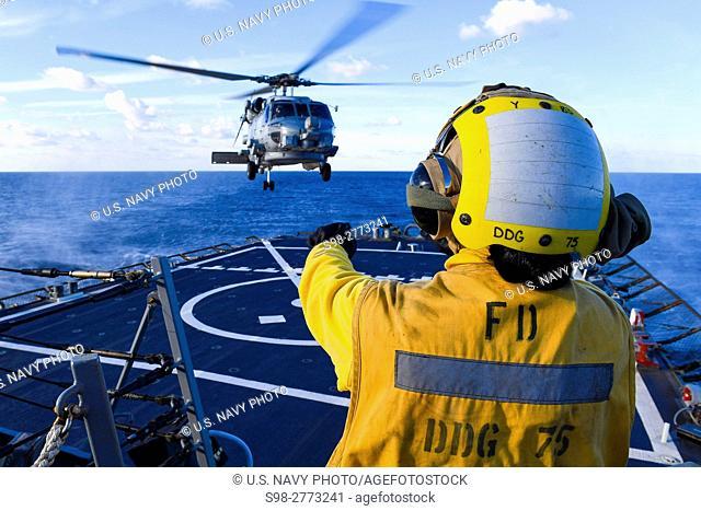 MEDITERRANEAN SEA (Dec. 15, 2016) - Petty Officer 3rd Class Dyamond P. Khammanivong, from Boston, signals to an SH-60B Sea Hawk, attached to USS Nitze (DDG 94)