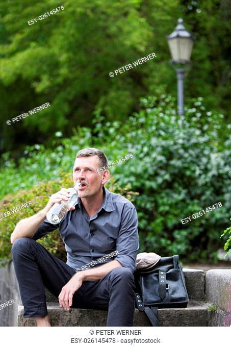 man sitting in park and drinking water