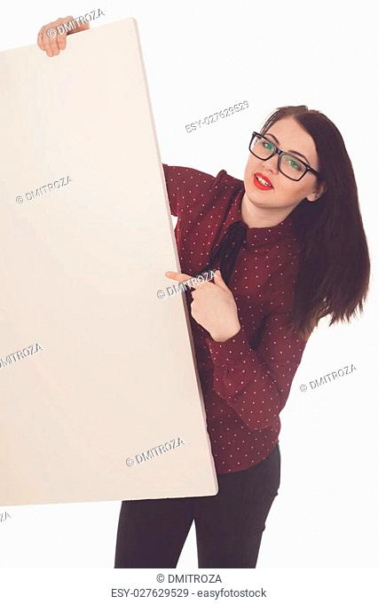 Woman with black glasses and red lips is holding a blank canvas in her hands and points on it against of white background