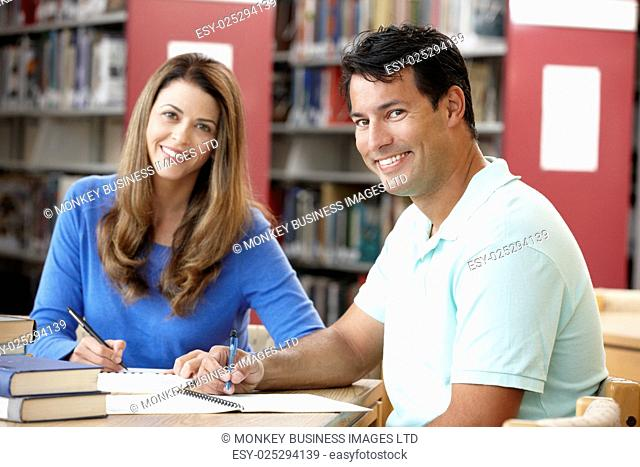 Mature students working in library