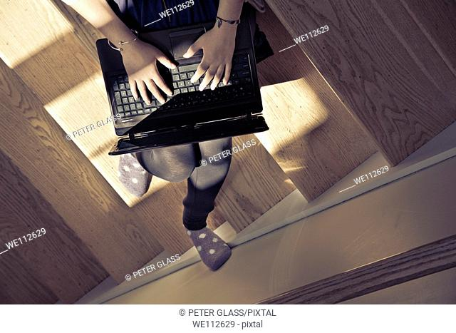 Teen girl, sitting on her house stairs, working on her laptop computer