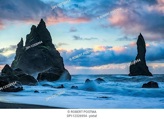 The sea stacks known as Reynisdrangar with waves and sunrise happening above them, South Coast; Iceland