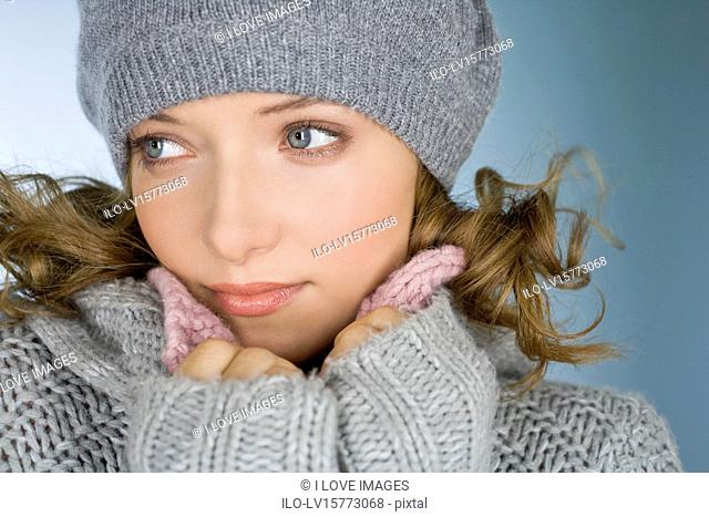 A young woman wearing a grey woollen hat, trying to keep warm