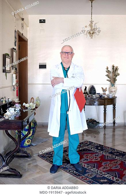An obstetrician standing in a room with knick-knacks resting on tables. Palermo (Italy), March 2014