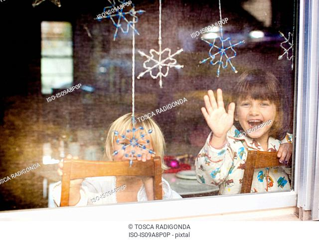 Children laughing and waving at window with dangling snowflakes
