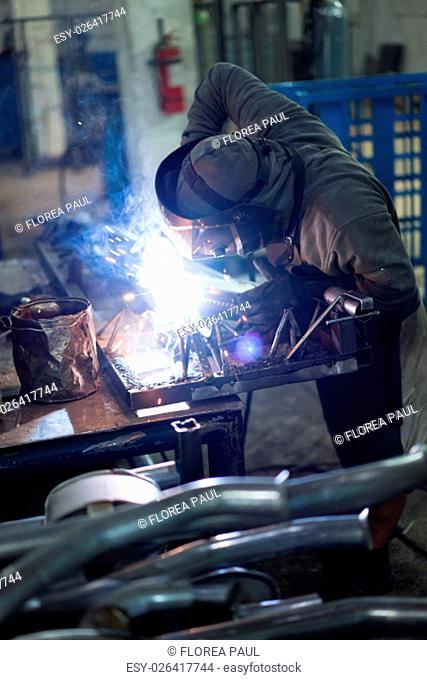left side descending view of a worker wearing protective gear, with mask, leather apron and gloves, welding together pieces of an exhaust pipe
