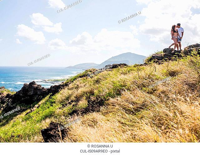 Young couple kissing on cliff top on Makapuu coast path, Oahu, Hawaii, USA