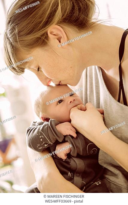 Mother testing newborn babyÔÇÖs hunger with her finger and kissing its forehead