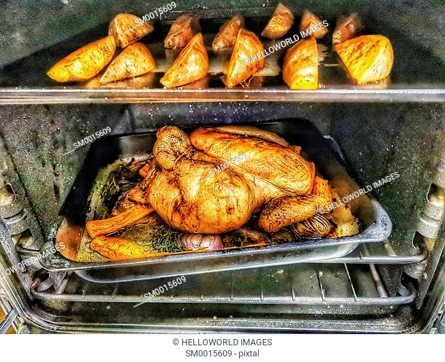 Sweet potato wedges and roast chicken with red onions and carrots in oven