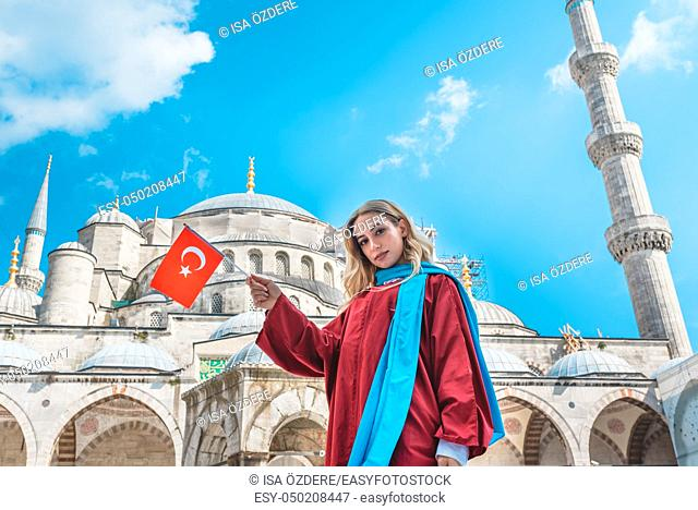 Attractive beautiful girl with covered clothes hold Turkish flag in front of Sultan Ahmet Mosque in Istanbul, Turkey. Travel Concept