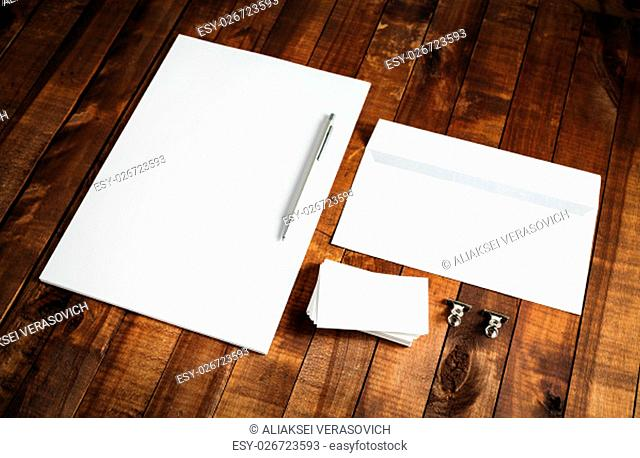 Photo of blank letterhead, business cards, envelope and pen on vintage wooden background. Blank stationery and corporate identity template