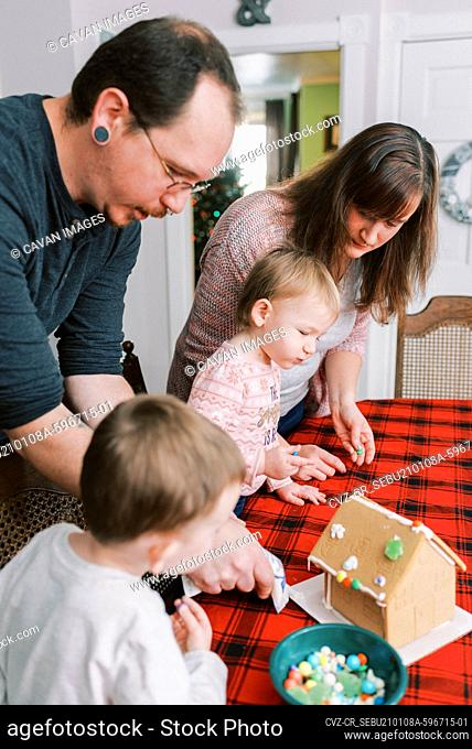 Family with little children decorating a gingerbread house in December