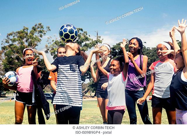Schoolgirl soccer team watching player balancing soccer ball on nose on school sports field
