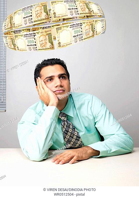 Executive thinking surrounded by flying money MR779K