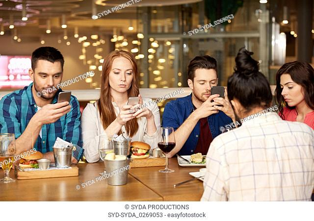 friends with smartphones at restaurant
