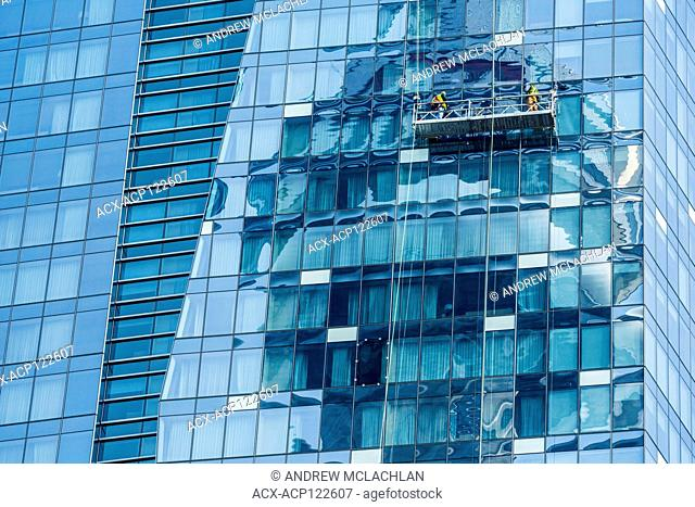 Window cleaners and building reflecting the CN Tower in Toronto, Ontario, Canada
