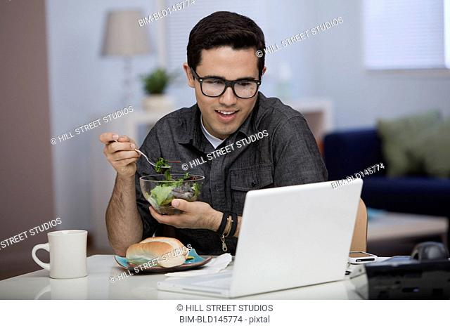 Hispanic man eating lunch and working on laptop