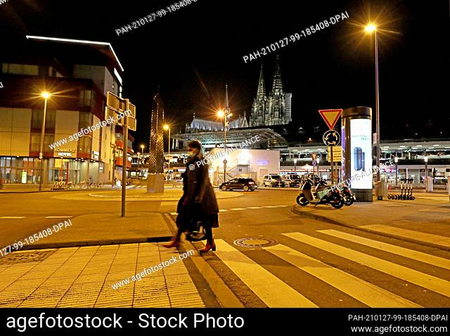 27 January 2021, North Rhine-Westphalia, Cologne: A woman walks across a crosswalk in the morning. Chancellor Merkel and the heads of state governments have...