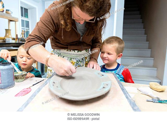 Potter painting platter watched by sons