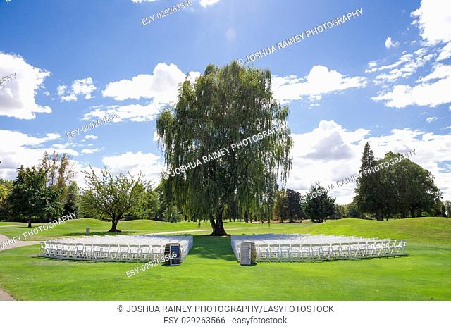 Wedding venue at a golf course with white chairs for the guests and a beautiful weeping birch tree as the main focal point of the ceremony