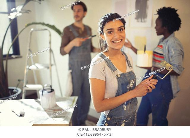 Portrait smiling young woman painting living room with friends