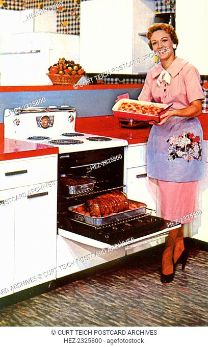 Here's General Electric's Compact Spacemaker oven, USA, 1955. A woman in a shirtwaist dress, high heels and apron in a kitchen