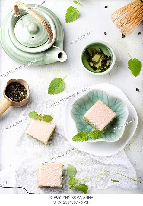 Matcha green tea cakes with white chocolate glaze and sesame seeds with a cup of green tea and balm, mint leaves