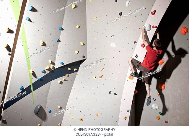 Mid adult male bouldering on climbing wall
