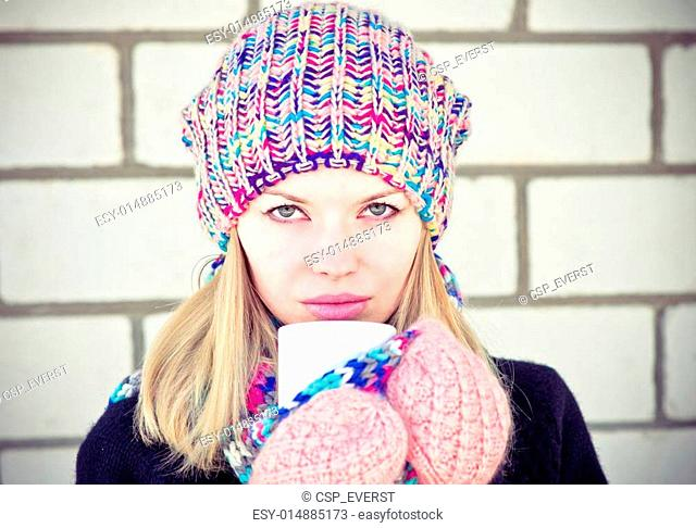 Young beautiful Woman drinking hot coffee wearing winter knitted hat and mittens clothing Lifestyle concept with white brick wall on background