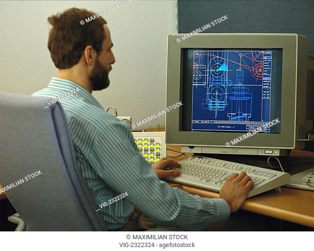 Engineer creating a computer-aided design of a machine part on a computer display sceen, - 01/01/2010