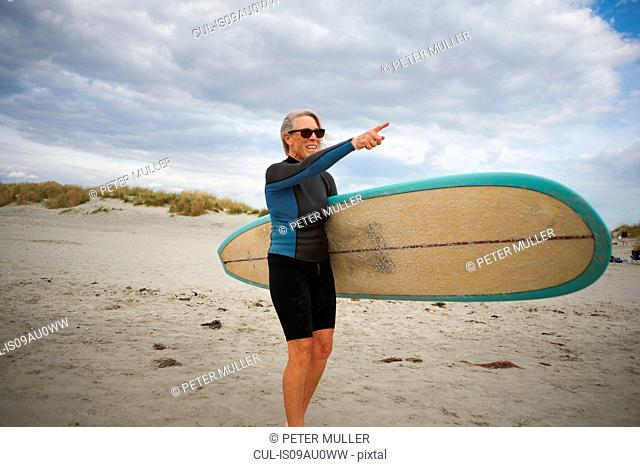 Senior woman standing on beach, holding surfboard, pointing to sea