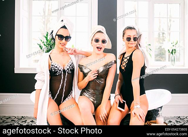 Theme female friendship. Party girlfriends, relaxation and spa procedures, hen party. Three Caucasian beautiful women sitting inside on bathroom in sunglasses