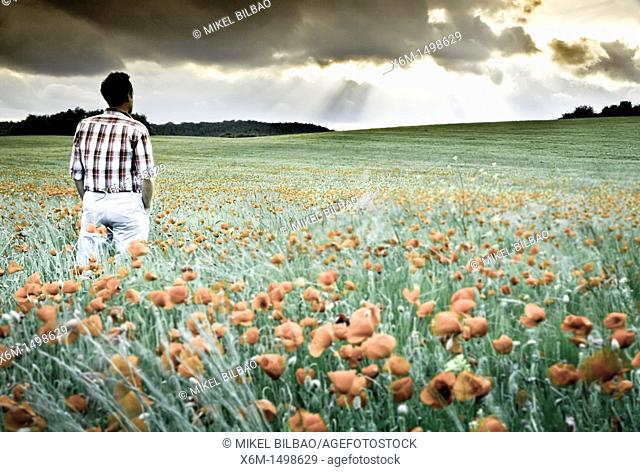 Young man looking the storm on a grassland