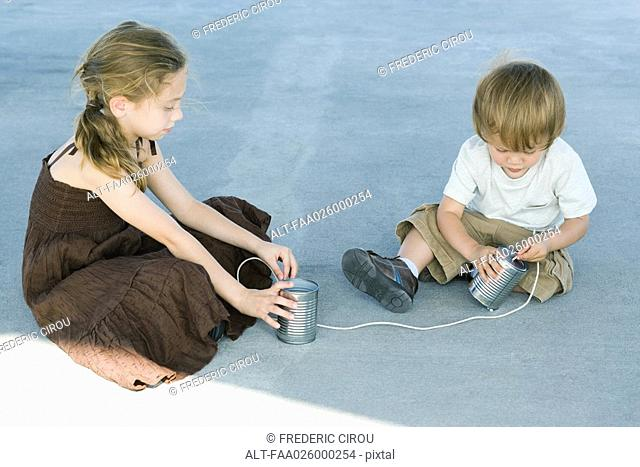 Brother and sister sitting on the ground, playing with tin can phone