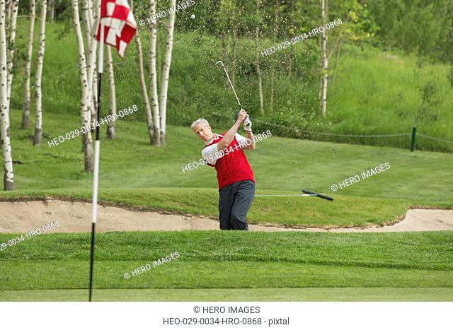 golfer hitting the golf ball out of a sand trap