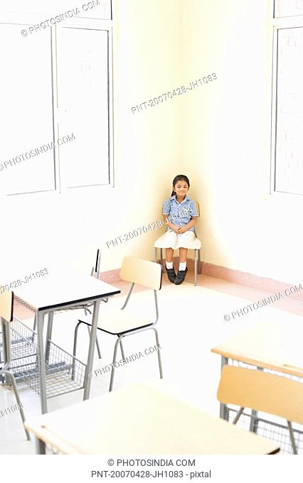 Schoolgirl sitting on a chair in a classroom