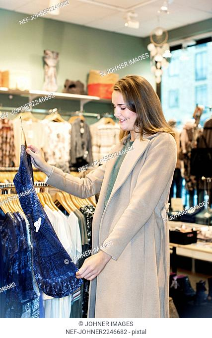 Woman checking blouse in shop