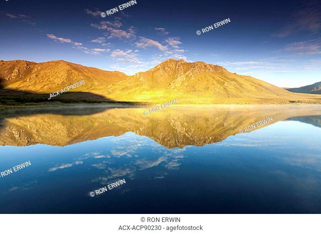Mountain reflections in the Blackstone Uplands of the Ogilvie Mountains in Tombstone Territorial Park, Yukon, Canada