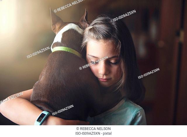 Girl hugging boston terrier dog