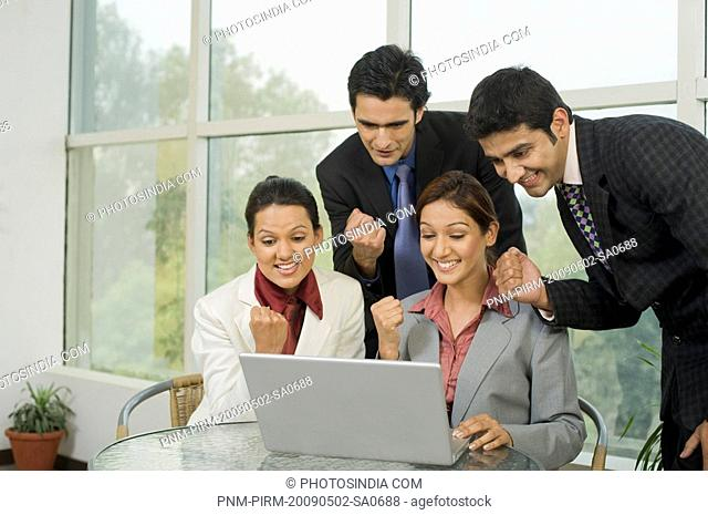 Business executives celebrating success in front of a laptop