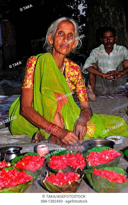 Woman selling flowers for pilgrims at the ghat by the Ganges River