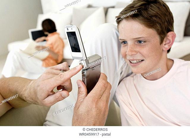 Close-up of a mans hand taking a picture of his son with a mobile phone