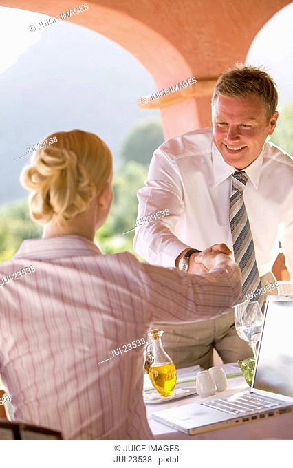 Businessman shaking hands with businesswoman over laptop