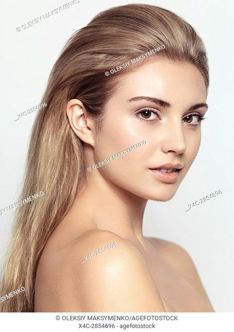 Beauty portrait of young exotic woman face with light brown hair and natural clean look isolated on light gray background