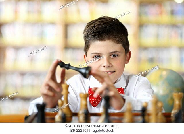 Boy considering a move while playing chess