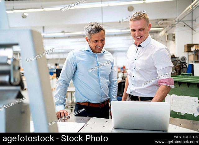 Two smiling colleagues using laptop in a factory